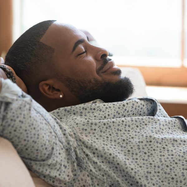 Calm lazy african american young man relaxing leaning on sofa at home, happy mindful guy holding hands behind head breathing fresh air lounge on couch enjoy stress free peaceful day with eyes closed